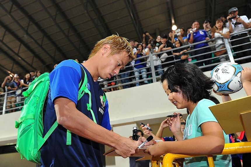 Keisuke Honda signing an autograph for a young fan at Bishan stadium. He is one of the many Europe-based players that coach Vahid Halilhodzic called up for the match against the Lions on Thursday.