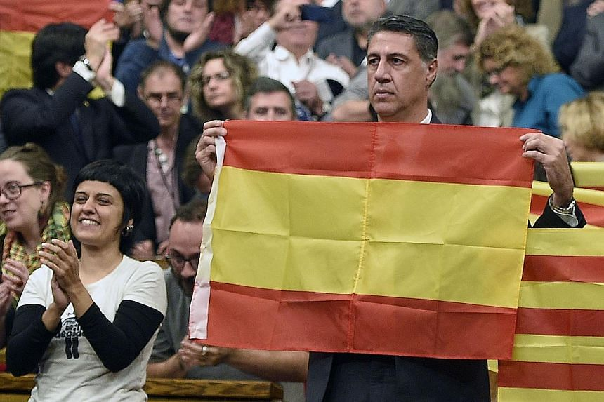 Mr Xavier Garcia Albiol of the pro-Madrid Popular Party, holding up a Spanish flag during a session at the Catalan Parliament in Barcelona after being out-voted yesterday on a proposed resolution to secede from the rest of the country. Spanish PM Mar