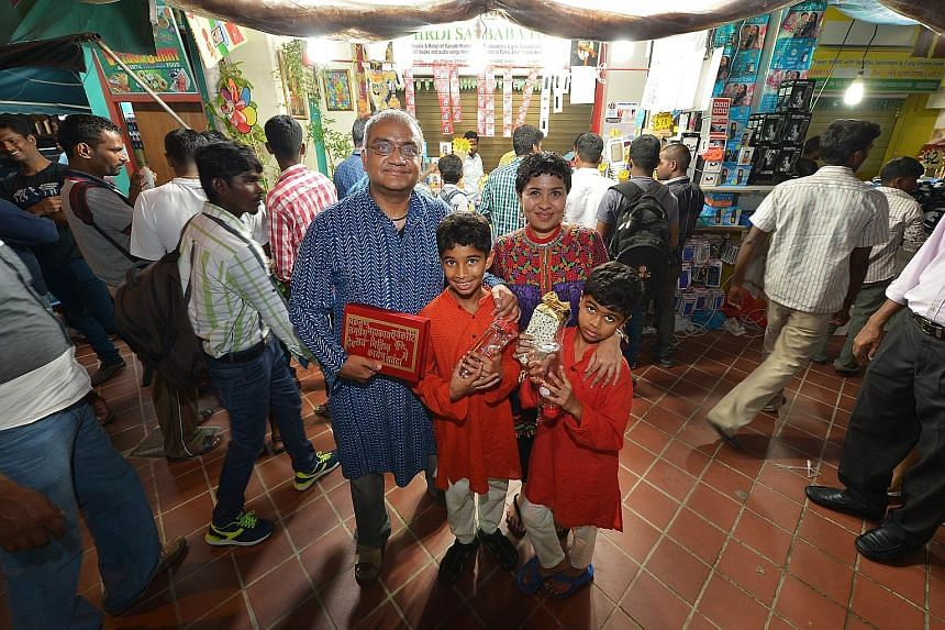 Ms Dipa, her husband Vish Srinivasan, 48, elder son Vihaan, 10, and younger son Kairav, eight, in Little India, with some of the items they are giving out to migrant workers this Deepavali.
