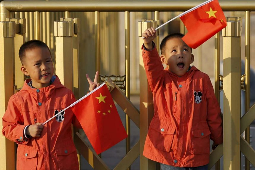 Twin boys Sun Qiyu and Sun Qichun hold China's national flags on the Tiananmen Gate in Beijing on Nov 2, 2015.