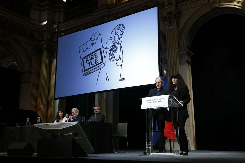 Chief editor of French satirical magazine Charlie Hebdo Gerard Biard (left) paying tribute to the victims of the Charlie Hebdo attacks, on Oct 26 in Paris.