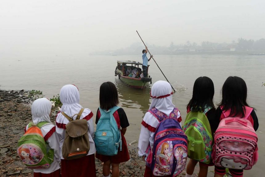 Students waiting for a boat ride to cross a river shrouded in haze in Palembang, South Sumatra, Indonesia.
