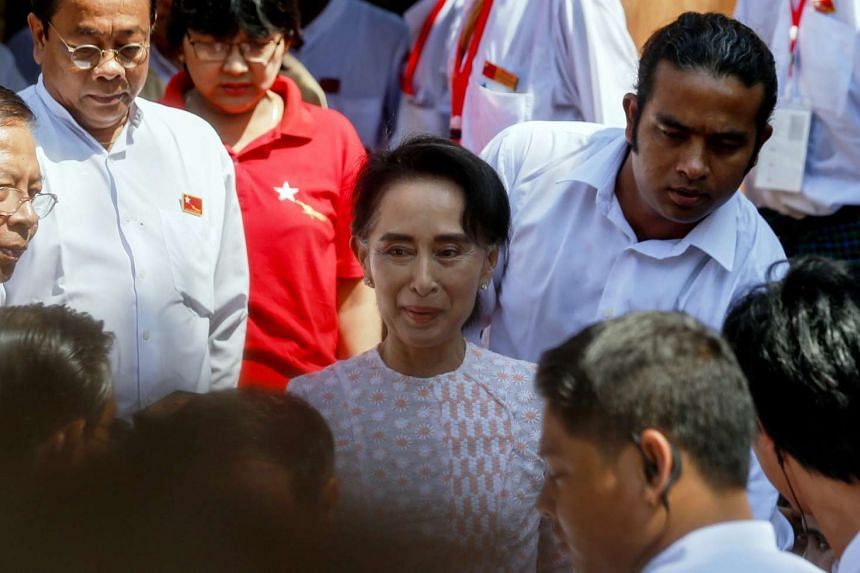 Ms Aung San Suu Kyi (centre), chairman of the National League for Democracy (NLD) party, leaving the NLD headquarters.