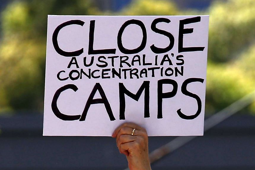 A protester holds a placard during a rally in support of refugees in Sydney on Oct 19, 2015.