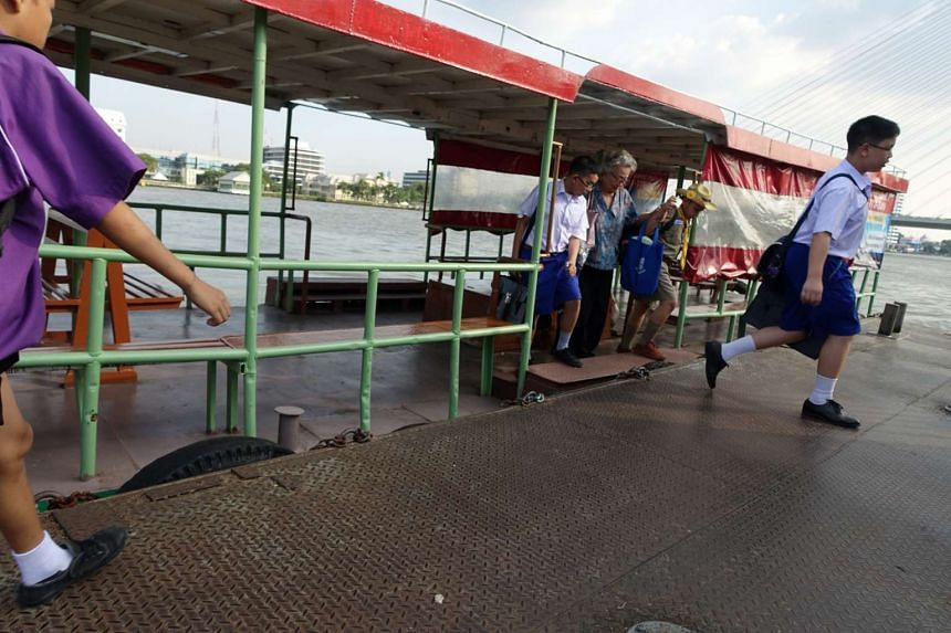 (Above) Commuters getting off a boat that plies the Chao Phraya River.