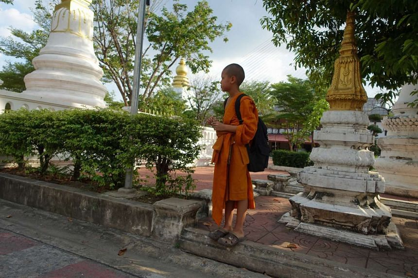 A novice monk waiting for a ride by Kharuehabodhi temple on the western bank of the river. Both banks of the Chao Phraya River are dotted with temples.