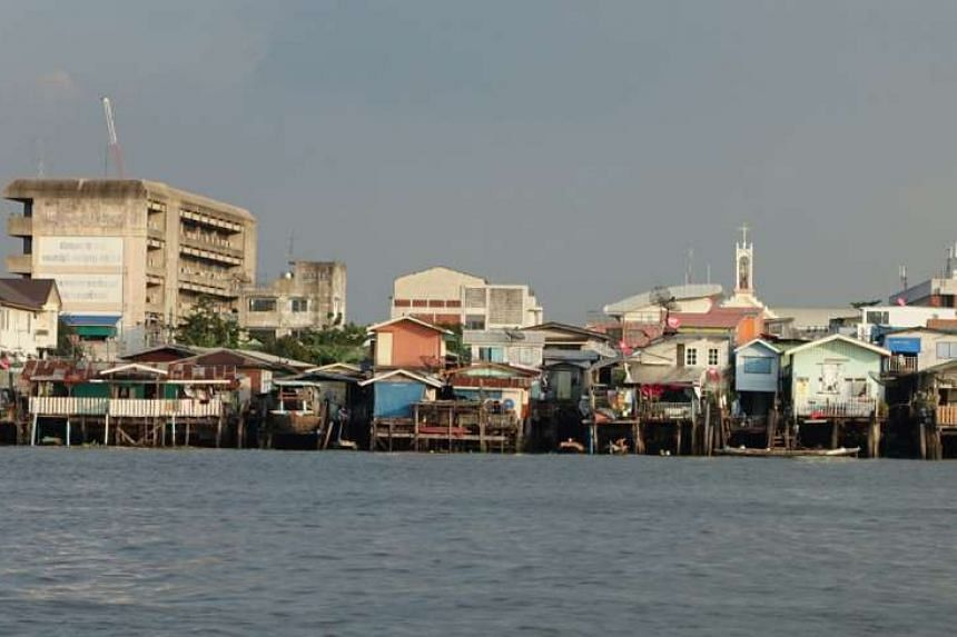 Wooden homes on stilts overlooking the Chao Phraya River's eastern bank. The Bangkok Metropolitan Administration estimates that fewer than 500 people would be relocated for the promenade to be built along the banks of the river.