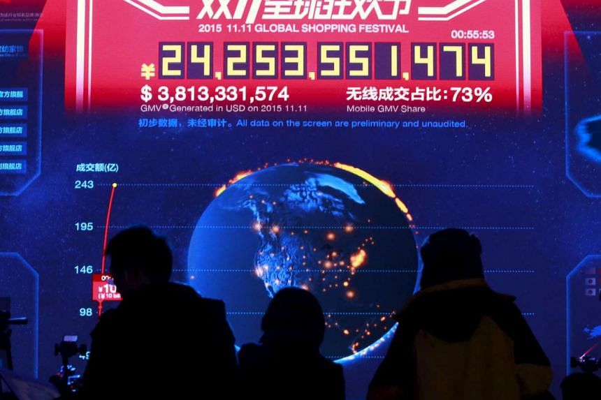 Journalists look at a screen showing real-time data of transactions at Alibaba Group's 11.11 Global shopping festival in Beijing.