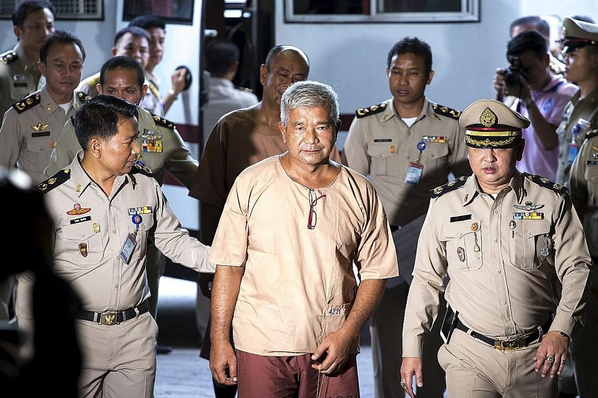 An impassive Manas Kongpan (centre), the most high-profile defendant, being led into court in Bangkok yesterday.