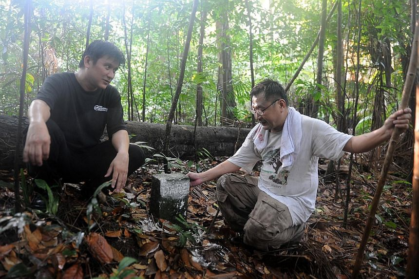 Mr Charles Goh (far left), 47, and Mr Raymond Goh, 51, who are researching Bukit Brown and its vicinity, discovered the significance of two markers, which pieced together the story of Mr George Mildmay Dare and Mr Seah Eu Chin, who were among the fir