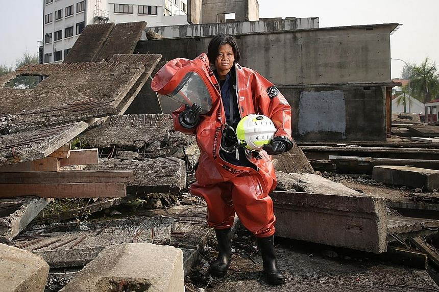 Senior SCDF instructor and firefighter Rennysa Ithnin in a protection suit against hazardous materials at a training facility.
