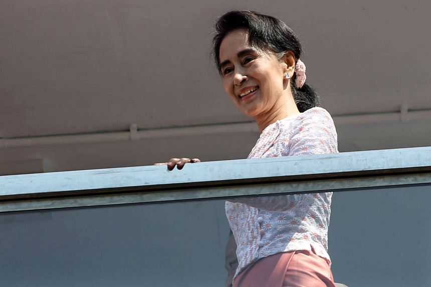 Aung San Suu Kyi stands on a balcony at the National League for Democracy party's headquarters in Yangon.