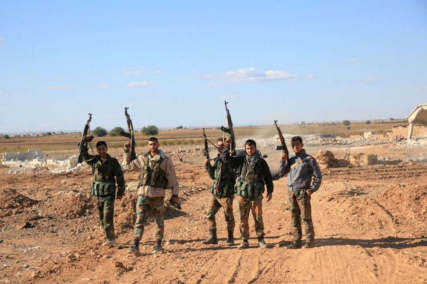 A group of Syrian pro-governement forces raise their guns in celebration on the outskirts of Kweyris.