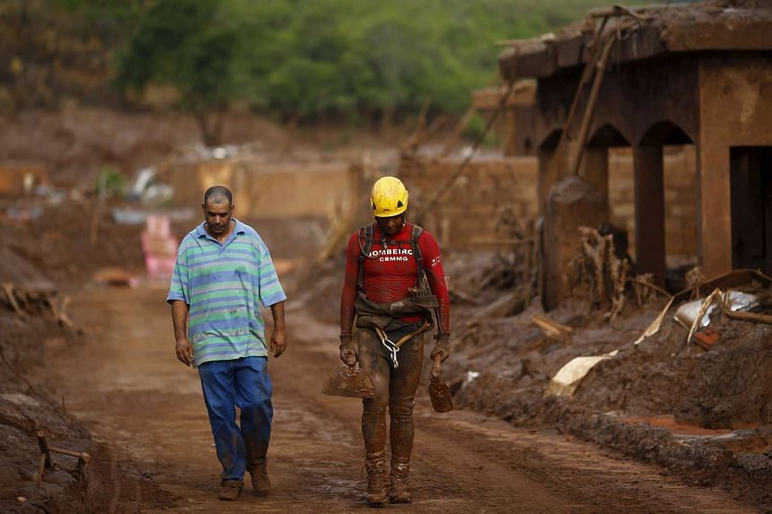Albertino Damasceno walks next to a rescue worker after spending nine hours searching for his son.