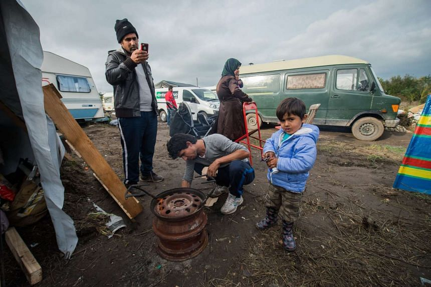 """A refugee family gathers in the migrant camp called """"The Jungle"""", in Calais, France on Nov 8, 2015."""