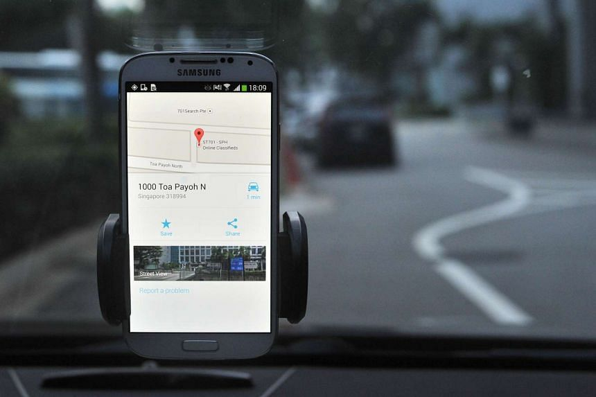 A Samsung smartphone showing Google Maps is mounted on the windscreen of a car.