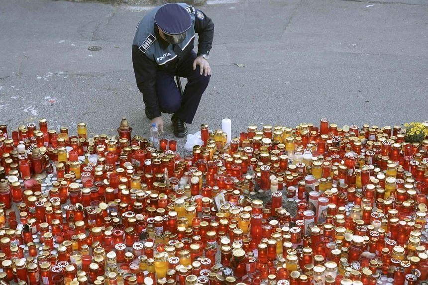 A policeman places a candle at a memorial commemorating the victims of a nightclub fire in Bucharest, Romania.