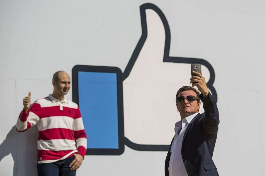 Visitors take a selfie in front of the Like logo displayed at the entrance of Facebook headquarters in California.