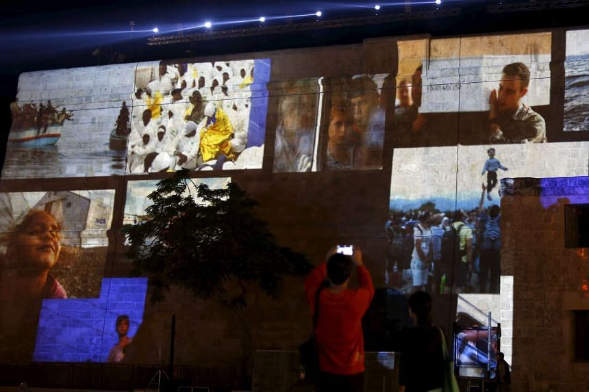 People taking pictures of projections showing images of migrants during a rehearsal of the opening ceremony of the 2015 Valletta Summit on Migration in Valletta, Malta, on Nov 10, 2015.