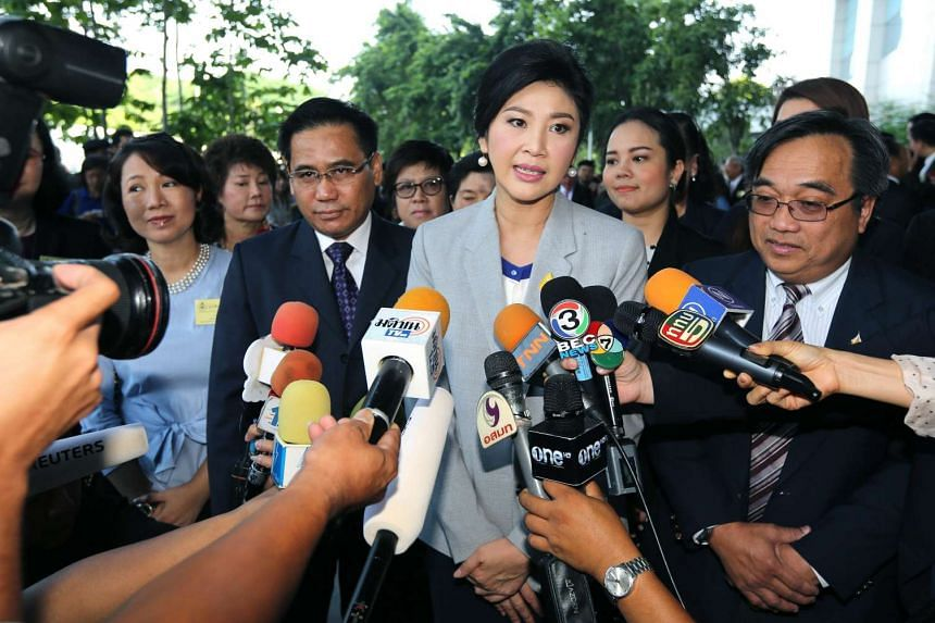 Former Thai PM Yingluck Shinawatra (centre) speaking to reporters as she arrives for a trial on criminal charges stemming from her government's rice price subsidy, on Oct 29, 2015.