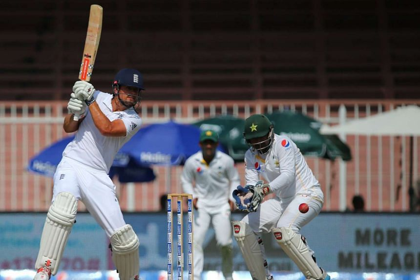 England's Alastair Cook (left) playing a shot past Pakistan's Sarfraz Ahmed during the fifth day of the third cricket Test match on Nov 5, 2015.
