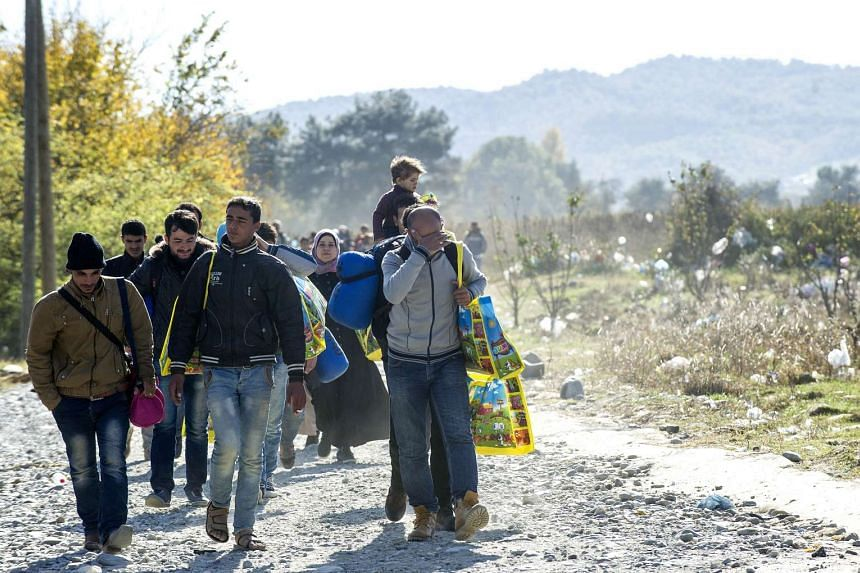 Migrants and refugees cross the Greek-Macedonian border near Gevgelija.