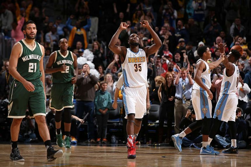 Kenneth Faried (centre) of the Denver Nuggets celebrates after he gave his team a 103-102 win on Nov 11,2015.