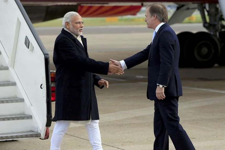 India's Prime Minister Narendra Modi is greeted by Britain's Minister of State for the Foreign and Commonwealth Office, Hugo Swire.