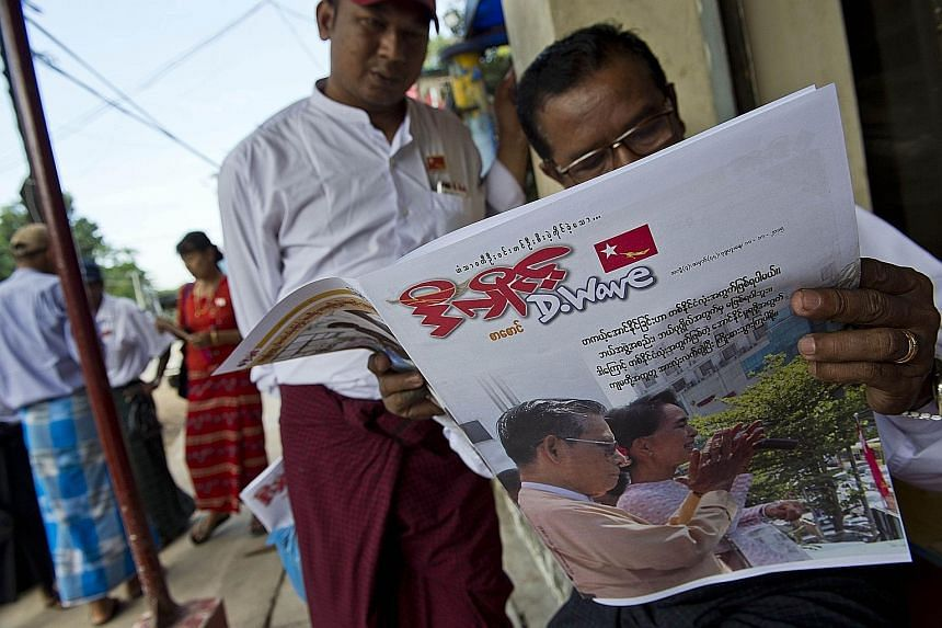 Myanmar residents reading a newspaper with a picture of opposition leader Aung San Suu Kyi and National League for Democracy party chairman Tin Oo outside the NLD headquarters in Yangon. Analysts believe the party is headed for a solid mandate to for