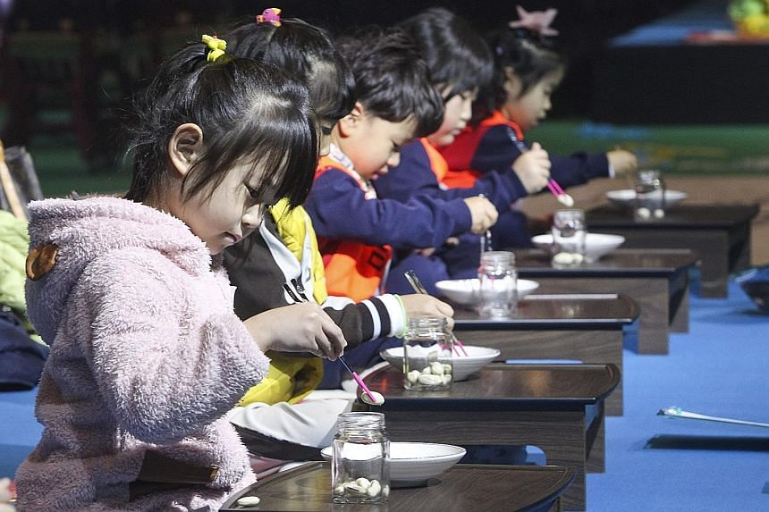 Children using chopsticks to transfer beans from a container to a plate in a contest held in Cheongju, some 135km south of Seoul, in South Korea, yesterday. The contest was part of the 2015 Chopstick Festival, billed by organisers as the first of its