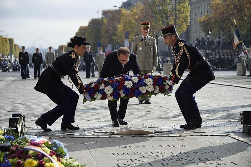 French President Francois Hollande (centre) laying a wreath at the Tomb of the Unknown soldier during Armistice Day ceremonies, which mark the 97th anniversary of the end of World War I, yesterday at the Arc de Triomphe monument in Paris. Officials a