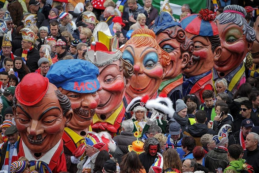 The Schwellkoepp (big heads made of papier mache) from the Mainz Carnival Association moving through the crowd in Mainz, Germany. The carnival season starts each year on Nov 11 at 11.11am and ends on Ash Wednesday of the following year. It is one of