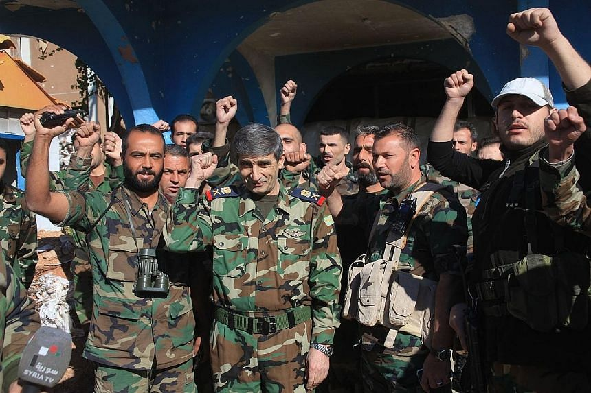 The Syrian army's Major-General Mounzer Zamam (centre) celebrating among soldiers at the Kweyris military airbase, in the northern Syrian province of Aleppo, yesterday.