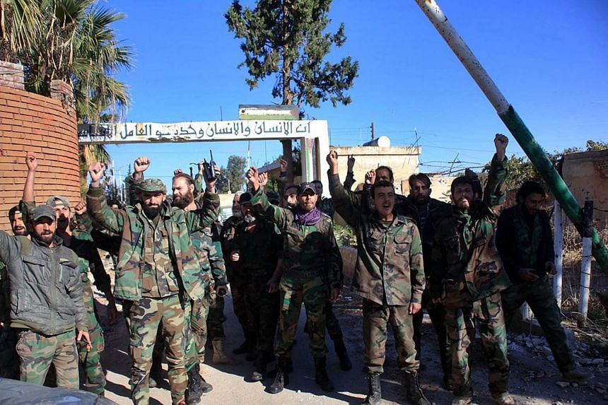 Soldiers from the Syrian Arab Army (SAA) celebrating after entering the Air Force Academy and airport at the Kwairis Military Airport, in eastern Aleppo, Syria, on Nov 11, 2015.