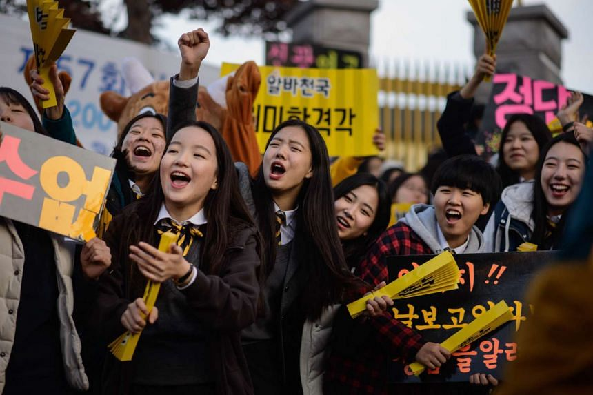 Students gather to greet others arriving to sit the annual college entrance exam in Seoul on Nov 12, 2015
