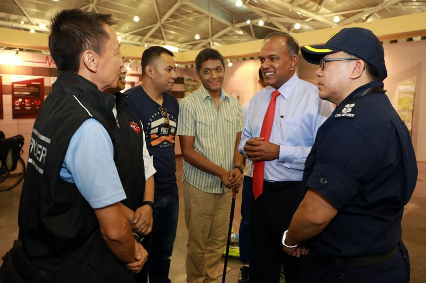 Home Affairs and Law Minister K Shanmugam speaks to volunteers under the Singapore Civil Defence Force's Neighbourhood Active Responder Programme (NEAR).