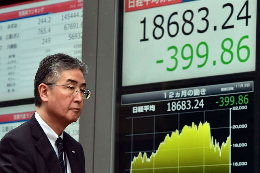 A man walking past a share prices board in Tokyo on Nov 2.