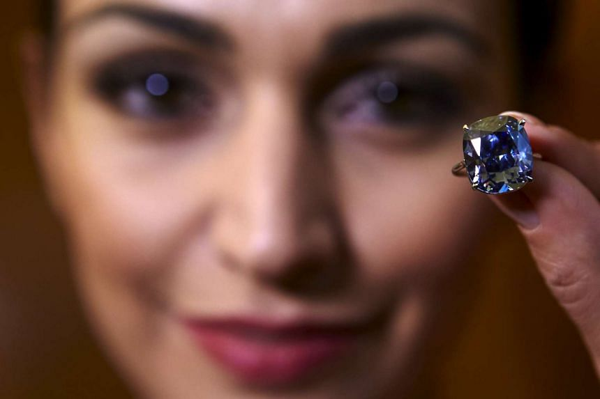 A model poses with a 12.03 carats cushion-shaped fancy vivid blue diamond mounted on a ring at Sotheby's auction house in Geneva, Switzerland in this Nov 4, 2015 file photo.