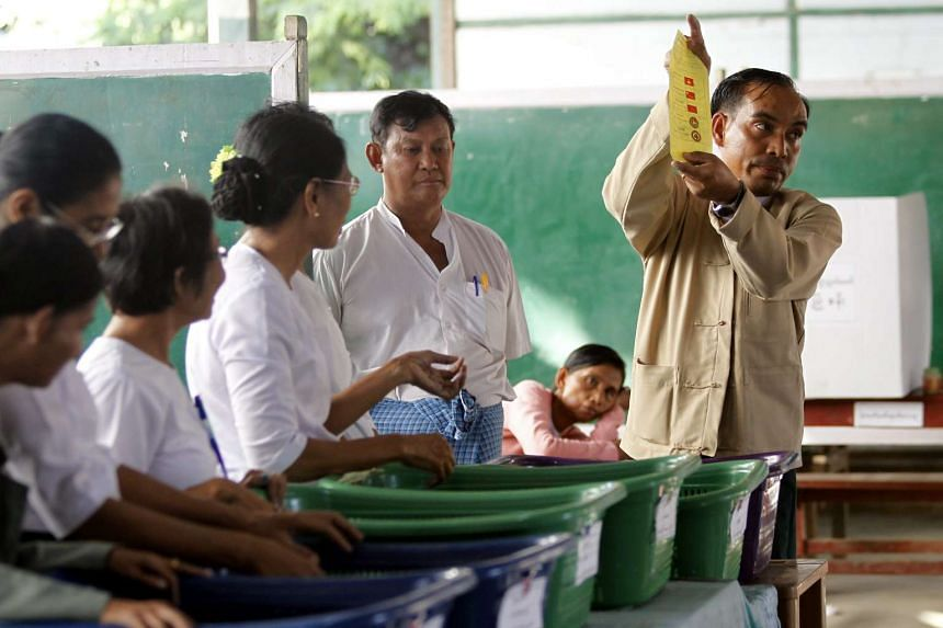 Election staff counting votes at a polling station in Mandalay on Nov 8.