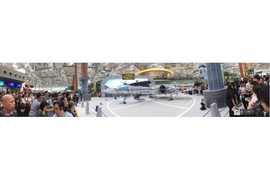 People waiting for the Star Wars event at Changi Airport to start. The T-70 X-wing fighter is seen in the centre.