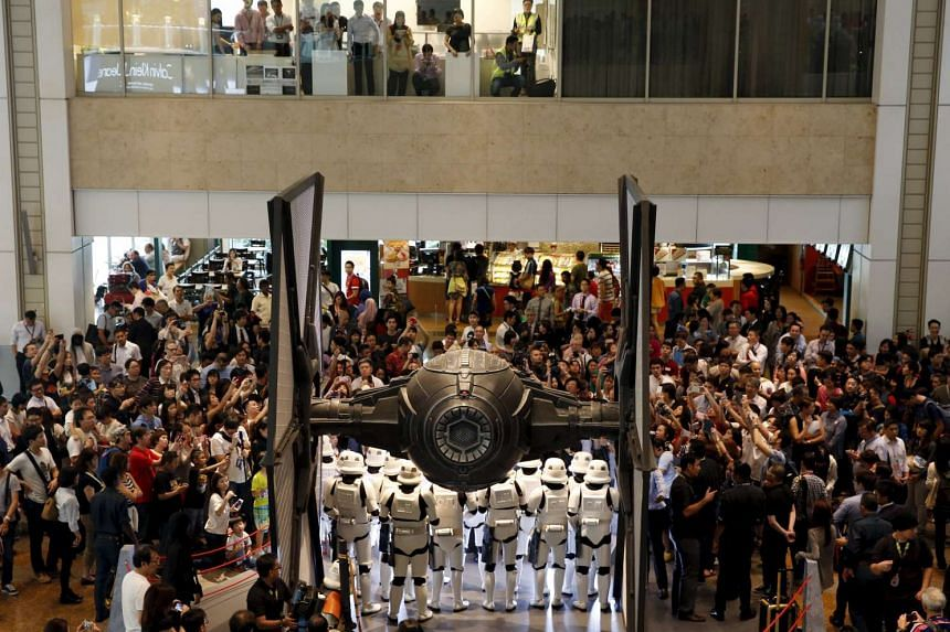 People take photos of Stormtroopers as they gather around a life-sized Star Wars TIE Fighter model on display at Singapore's Changi Airport on Nov 12, 2015.