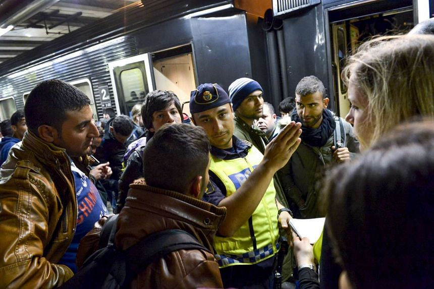 Migrant passengers get directions from a policeman after arriving by train in Stockholm.