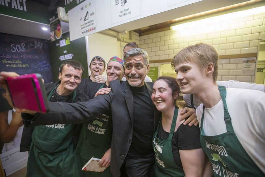 Actor George Clooney (centre) takes a selfie with staff of Social Bite cafe, which helps the homeless in Edinburgh, Britain, on Nov 12, 2015.