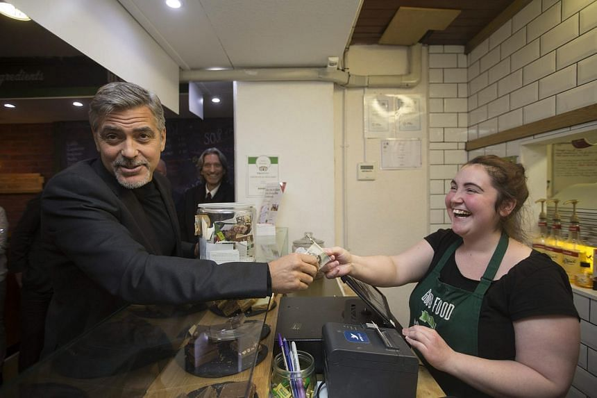 Actor George Clooney (left) hands over his money to Social Bite staff Ciara Whelan.