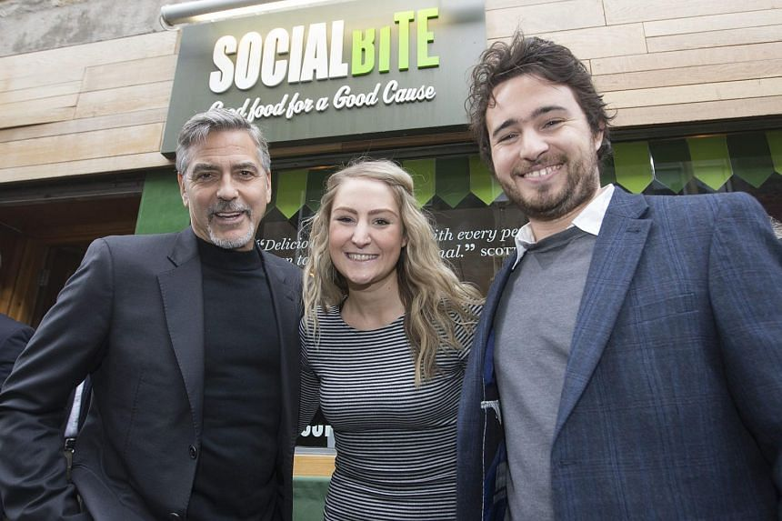 Actor George Clooney (left) posing for a photograph with Social Bite founders Josh Littlejohn (right) and Alice Thompson.