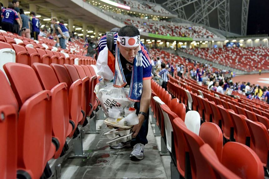 A Japanese spectator clears the rubbish after the match.