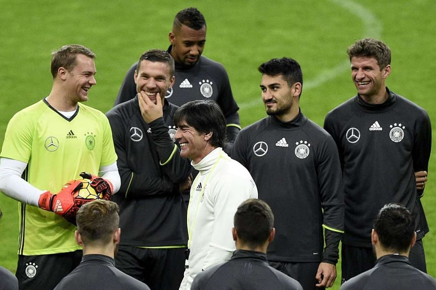 Germany's head coach Joachim Loew jokes with his players during a training session at the Stade de France stadium in Saint-Denis.