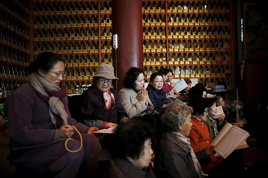 Relatives of students sitting entrance exams yesterday praying for success at a Buddhist temple in Seoul.