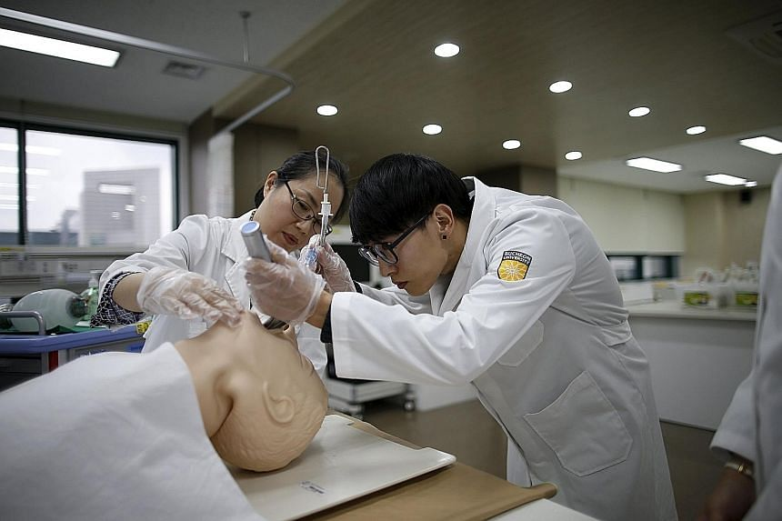 Nursing student Jang Dong Hae practising on a dummy during a lesson at Bucheon University in South Korea. He was formerly a finance undergraduate.