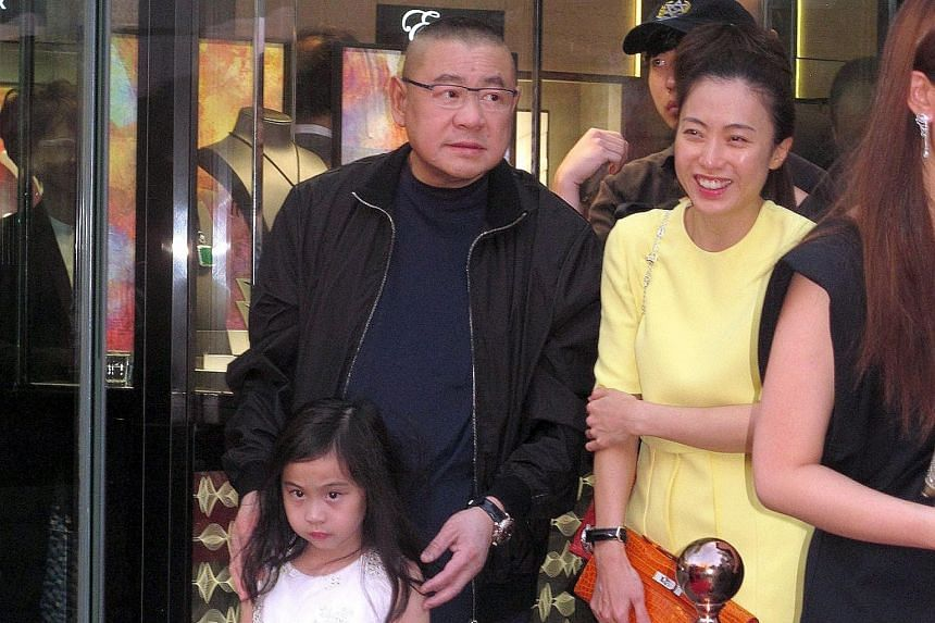 """Mr Joseph Lau (left) with girlfriend Chan Hoi Wan and their daughter Josephine in Hong Kong last year. He paid a record US$48.4 million for the 12.03-carat """"Blue Moon"""" diamond (top) at an auction on Wednesday, a day after he spent US$28.5 million on"""